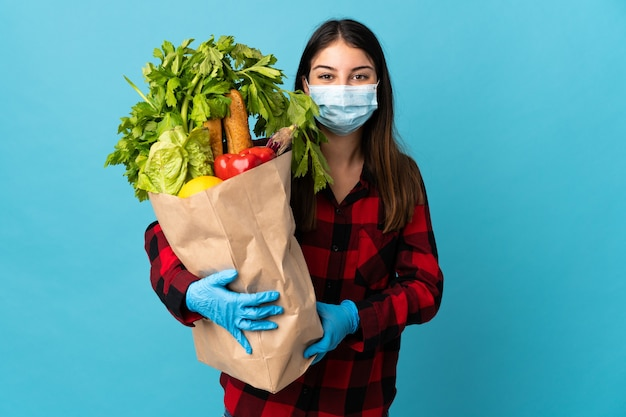 Młody kaukaski z warzywami i maską na niebiesko z happy wypowiedzi