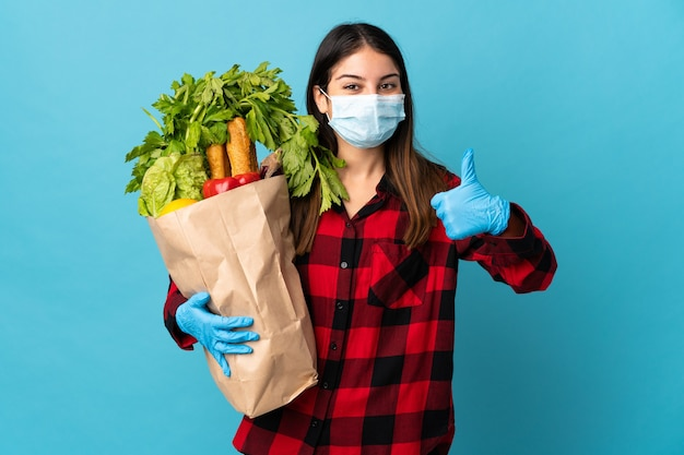Młody kaukaski z warzywami i maską na niebiesko z kciukami do góry, ponieważ stało się coś dobrego