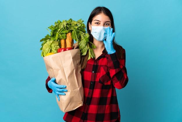 Młody kaukaski z warzywami i maską odizolowaną na niebiesko, krzycząc z szeroko otwartymi ustami