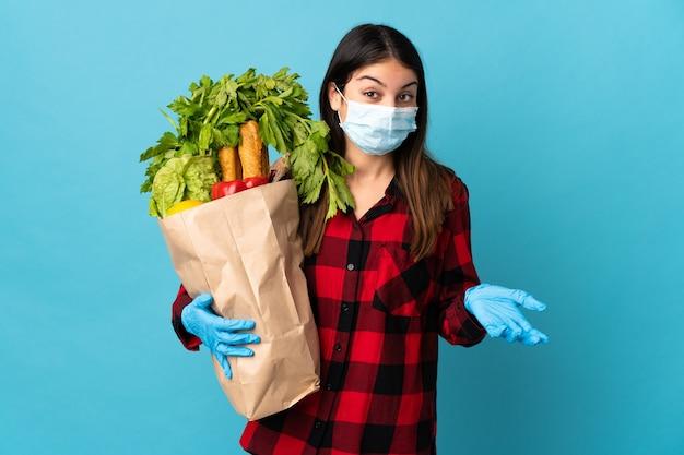 Młody kaukaski z warzywami i maską odizolowaną na niebiesko robi gest wątpliwości podczas podnoszenia ramion