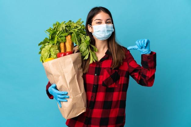 Młody kaukaski z warzywami i maską odizolowany na niebiesko dumny i zadowolony z siebie