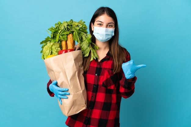 Młody kaukaski z warzywami i maską samodzielnie na niebiesko, wskazując na bok, aby przedstawić produkt