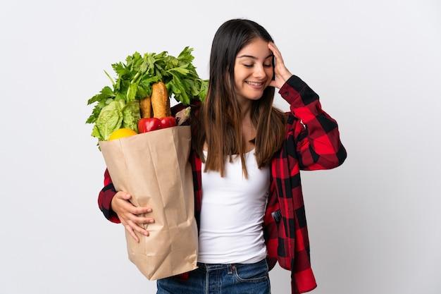 Młody kaukaski z warzywami na białym tle na białej ścianie dużo się uśmiecha