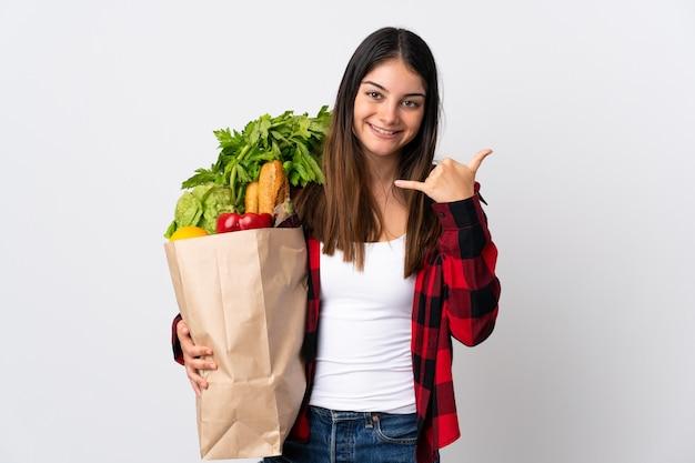 Młody kaukaski z warzywami na białym tle na białej ścianie dzięki telefonowi gestowi. oddzwoń do mnie znak