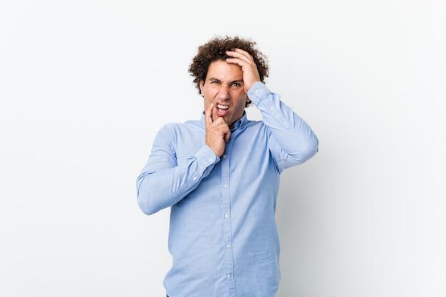 Młody, kędzierzawy dojrzały mężczyzna ubrany w elegancką koszulę jęczy i płacze niepocieszony.