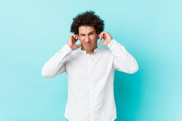 Młody kędzierzawy dojrzały mężczyzna ubrany w elegancką koszulę zakrywającą uszy rękami.