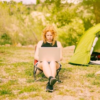 Młody kędzierzawy kobieta surfing na laptopie na naturze