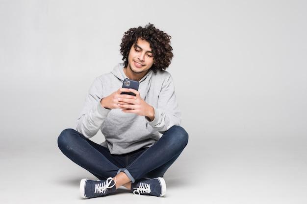 Młody kędzierzawy mężczyzna obsiadanie na podłoga wysyła wiadomość odizolowywającą na biel ścianie