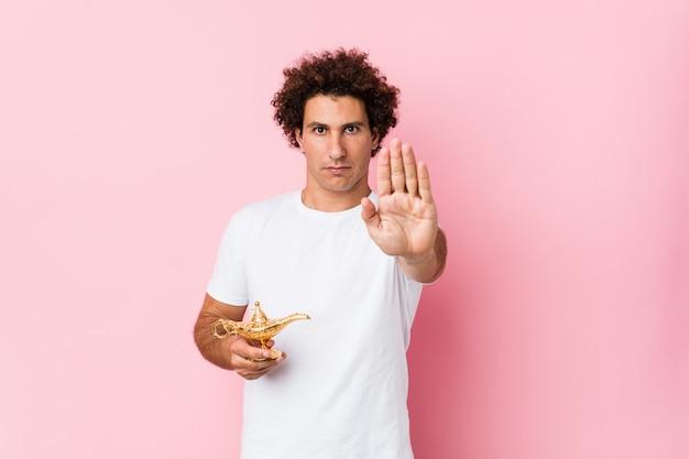 Młody kędzierzawy mężczyzna trzyma magiczną lampową pozycję z rozpostartą ręką pokazuje znak stopu, zapobiegając ci