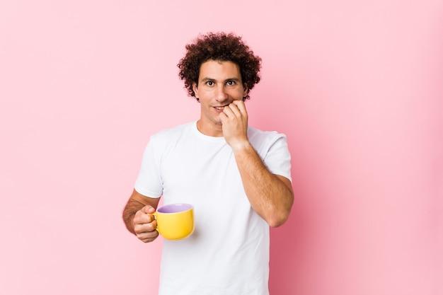 Młody kędzierzawy mężczyzna trzymający filiżankę herbaty obgryzający paznokcie, nerwowy i bardzo niespokojny