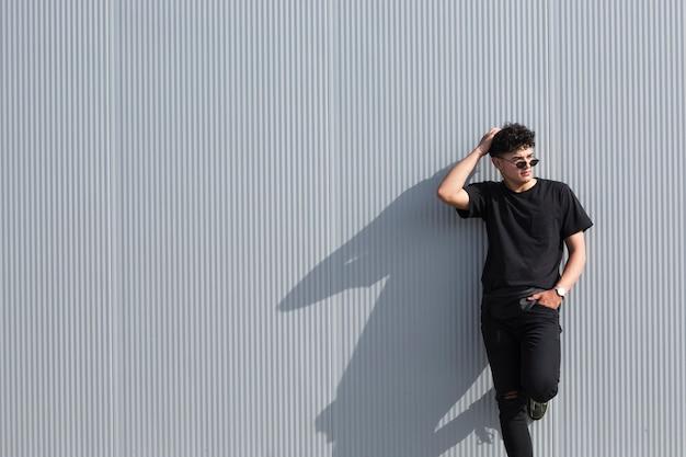 Młody kędzierzawy mężczyzna w okularach przeciwsłonecznych i czerni ubraniach opiera na popielatej ścianie
