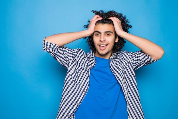 Młody kędzierzawy mężczyzna wręcza koszt stały odizolowywającego na błękit ścianie