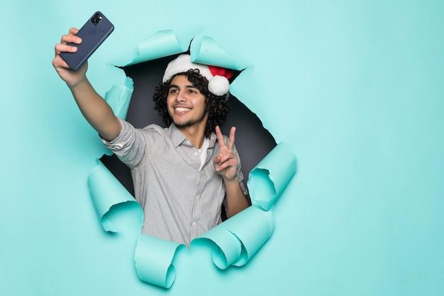 Młody kędzierzawy przystojny mężczyzna odzież w santa kapeluszu bierze selfie od dziury na zielonym papierze