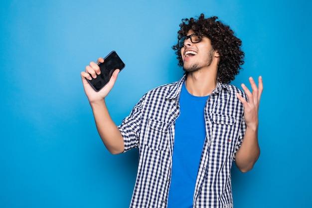 Młody kędzierzawy przystojny mężczyzna śpiewa na telefonie nad odosobnionym na błękit ścianie