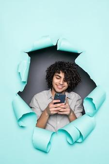 Młody kędzierzawy przystojny mężczyzna używa telefonu od dziury na zielonym papierze