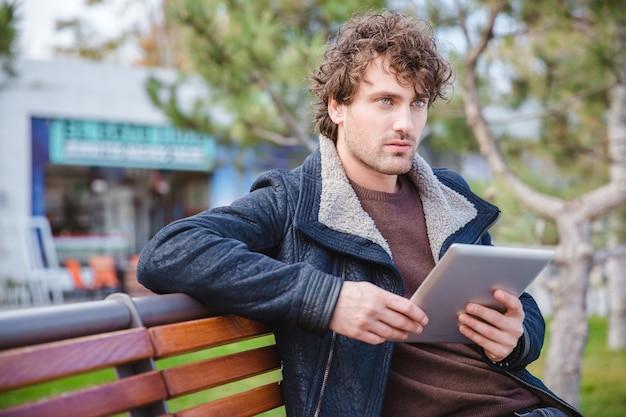 Młody kędzierzawy zamyślony, atrakcyjny, zamyślony mężczyzna siedzący na drewnianej ławce w parku i trzymający tablet