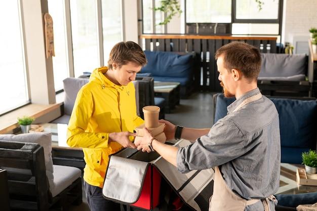 Młody kelner pomaga kurierowi w pakowaniu plecaka i wkładaniu pojemników z jedzeniem i napojami do dużej torby w restauracji