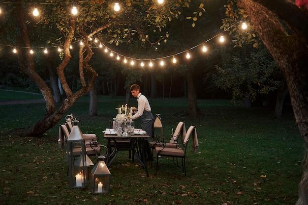 Młody kelner składa zamówienie. przygotowane biurko czeka na jedzenie i gości. porą wieczorową