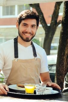 Młody kelner trzymając zasobnik