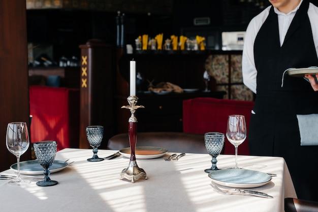 Młody kelner w stylowym mundurze zajmuje się obsługą stołu w pięknym zbliżeniu restauracji dla smakoszy. działalność restauracyjna na najwyższym poziomie.