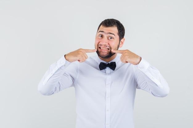 Młody kelner wskazujący palcami na zęby w białej koszuli i wyglądający wesoło. przedni widok.