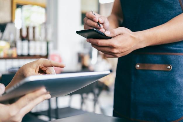 Młody kelner za pomocą cyfrowego tabletu, aby pokazać menu klientowi.