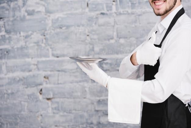 Młody kelnera mienia talerz z ceglanym tłem