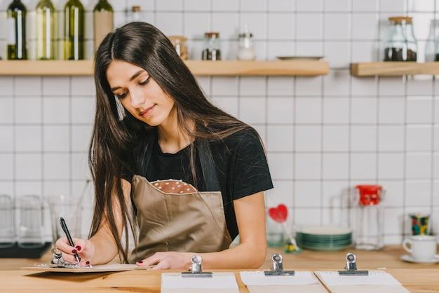 Młody kelnerki writing na schowku