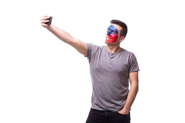 Młody kibic czeskiej piłki nożnej bierze selfie na białej ścianie