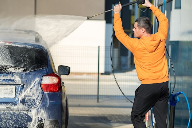 Młody kierowca człowiek mycie samochodu za pomocą bezdotykowego strumienia wody pod wysokim ciśnieniem w samoobsługowej myjni samochodowej.