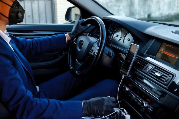 Młody kierowca mantaxi w masce medycznej i jednorazowych gumowych rękawiczkach siedzi za fotelem kierowcy w samochodzie