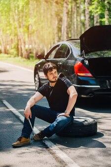 Młody kierowca płci męskiej siedzi na kole zapasowym na drodze