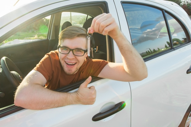 Młody kierowca pokazuje kluczyki do samochodu i kciuki do góry szczęśliwy. mężczyzna trzyma kluczyk do nowego samochodu. wynajem samochodów lub koncepcja prawa jazdy z mężczyzną jazdy w pięknej przyrodzie na podróż.