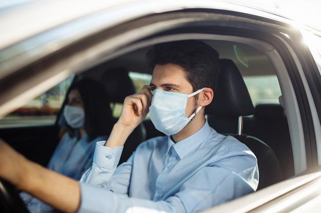 Młody kierowca taksówki dostosowuje sterylną maskę medyczną w samochodzie. koncepcja pandemii koronawirusa.