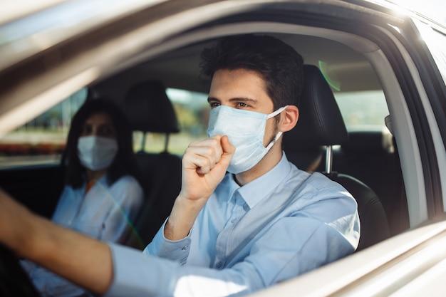 Młody kierowca taksówki kaszle do sterylnej maski medycznej w samochodzie. koncepcja pandemii koronawirusa.