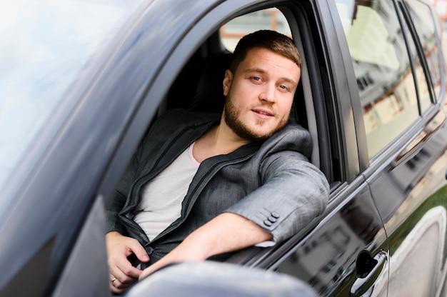 Młody kierowca z otwartym oknem samochodu