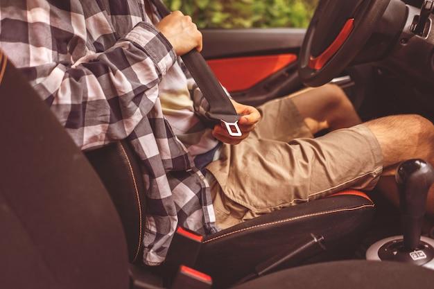 Młody kierowca zapinający pas bezpieczeństwa w samochodzie