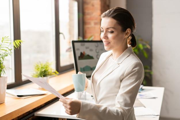 Młody kierownik biura w eleganckim garniturze, czytając lub analizując papier i pijąc herbatę stojąc przy biurku