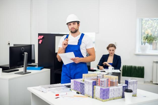 Młody kierownik budowy robi notatki w biurze
