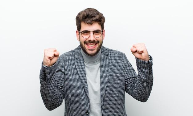 Młody kierownik człowiek czuje się szczęśliwy, pozytywny i udany, świętuje zwycięstwo, osiągnięcia lub powodzenia w białej ścianie