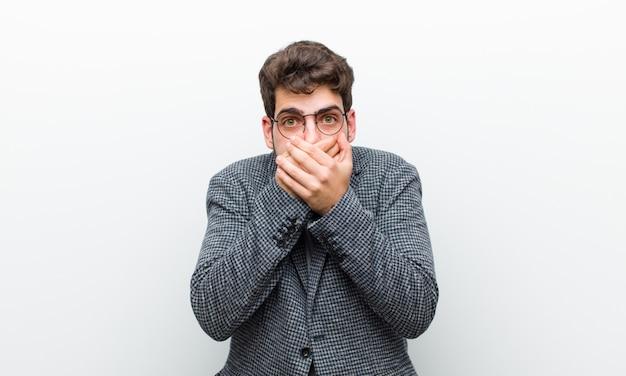 Młody kierownik człowiek obejmujący usta rękami z zszokowanym, zdziwionym wyrazem, zachowujący tajemnicę lub mówiąc: ups przeciwko białej ścianie