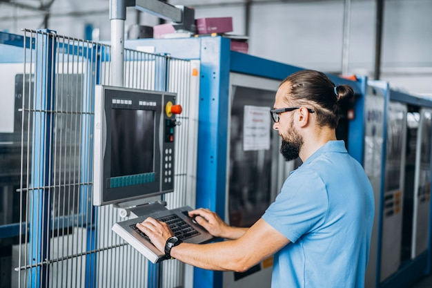 Młody kierownik inżyniera z brodą sprawdzającą manufakturę, miejsce pracy i maszyny w dużej fabryce.