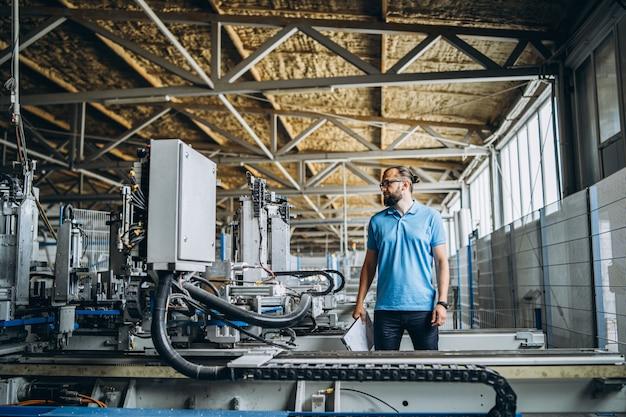 Młody kierownik inżyniera z manufakturą sprawdzania brody, miejscem pracy i maszynami w dużej fabryce.