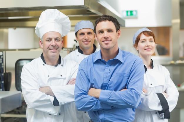 Młody kierownik pozuje z niektóre szefami kuchni