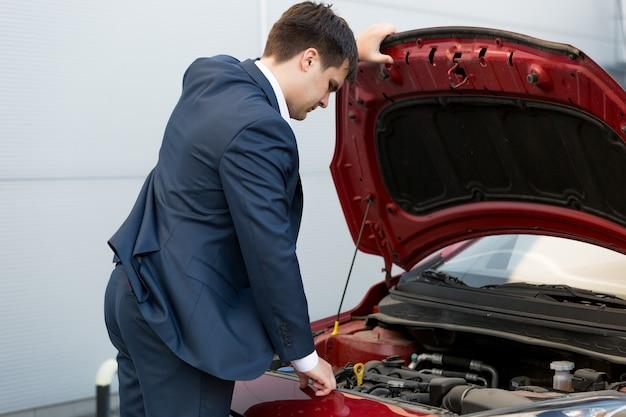 Młody kierownik sprzedaży samochodów patrzący pod maskę samochodu
