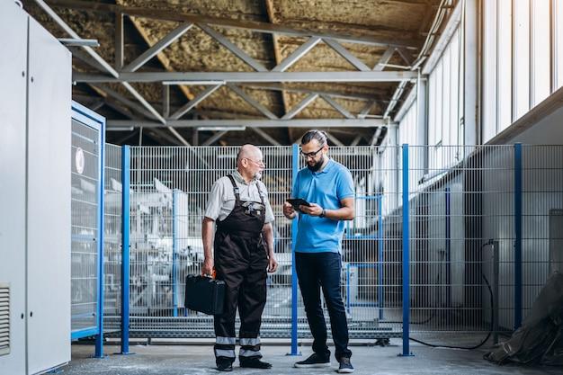 Młody kierownik z brodą pokazuje i sprawdza proces pracy dorosłego fachowego pracownika na dużej fabryce.