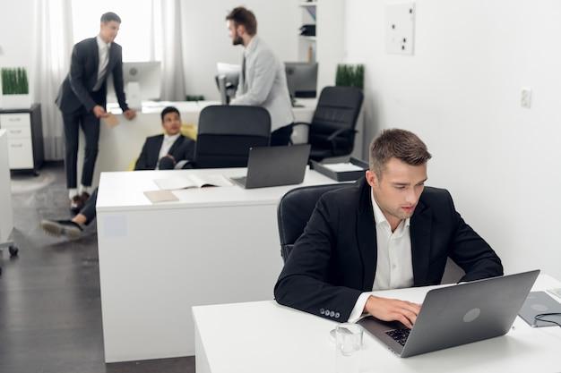 Młody kierownik zakupów w czarnym garniturze składa duże zamówienie online za pośrednictwem intranetu w laptopie swojej firmy.