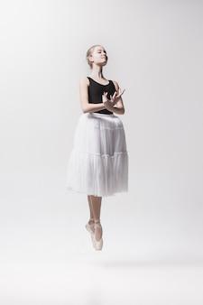 Młody klasyczny tancerz odizolowywający na biel przestrzeni.