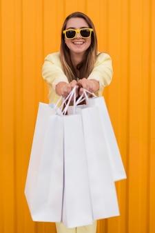 Młody klient nosi żółte ubrania pokazując jej torby na zakupy