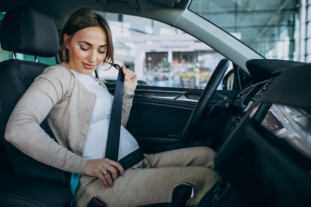 Młody kobieta w ciąży bada samochód w samochodowej sala wystawowej